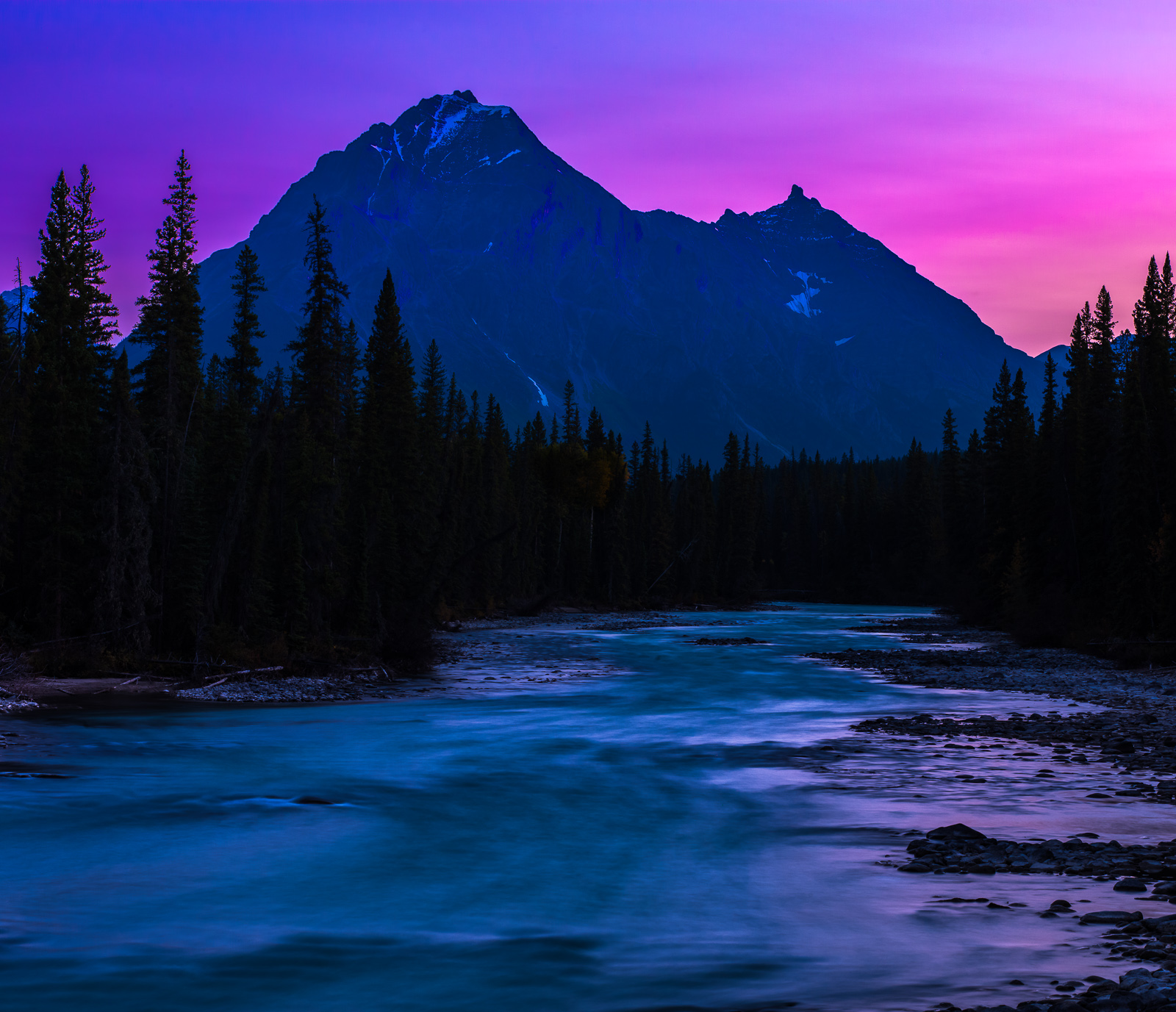 Sun setting behind the mountains with the last light filling the river blues hues as the night come-forth.