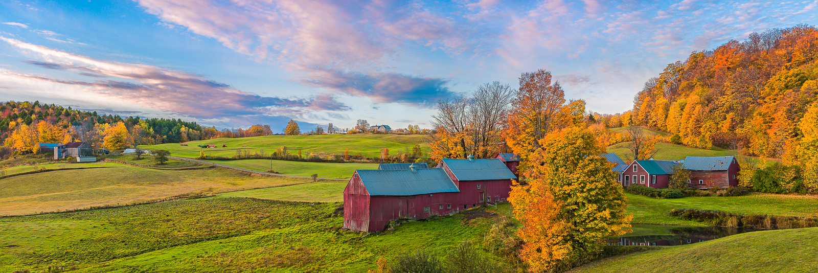 An old New England farm enjoys the bluebird color skies and vibrant autumn foliage.